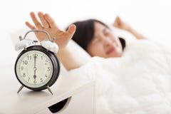 Mujer que apaga el despertador en la cama foto de archivo