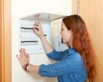 Mujer que apaga el interruptor de la luz fotos de archivo