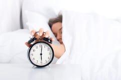 Mujer que apaga el reloj de alarma Imagen de archivo