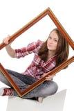 Mujer que aplaza un viejo marco Fotos de archivo