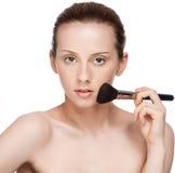 Mujer que aplica el cepillo cosmético Imágenes de archivo libres de regalías