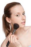Mujer que aplica el cepillo cosmético Fotos de archivo libres de regalías