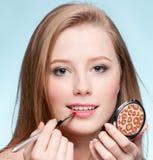 Mujer que aplica el cepillo cosmético del lápiz labial Fotos de archivo