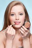 Mujer que aplica el cepillo cosmético del lápiz labial Imagenes de archivo