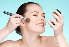 Mujer que aplica el cepillo cosmético del polvo Foto de archivo libre de regalías