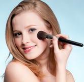 Mujer que aplica el cepillo de pintura cosmético Fotografía de archivo libre de regalías