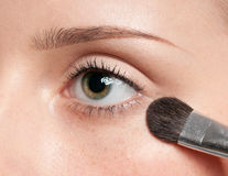 Mujer que aplica el cepillo de pintura cosmético en zona del ojo Imagen de archivo libre de regalías
