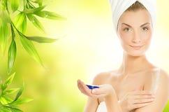 Mujer que aplica el cosmético orgánico Fotos de archivo