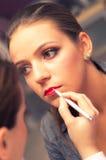 Mujer que aplica el lápiz labial Imagen de archivo libre de regalías