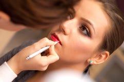 Mujer que aplica el lápiz labial Fotografía de archivo libre de regalías