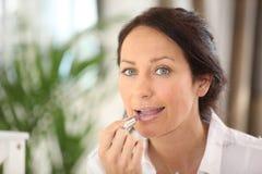 Mujer que aplica el lápiz labial Imagen de archivo