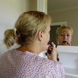 Mujer que aplica el lápiz labial Fotos de archivo libres de regalías