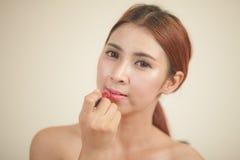 Mujer que aplica el lápiz labial Foto de archivo libre de regalías