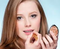 Mujer que aplica el lápiz labial cosmético Fotos de archivo libres de regalías