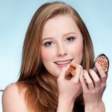 Mujer que aplica el lápiz labial cosmético Imagen de archivo libre de regalías