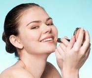 Mujer que aplica el lápiz labial cosmético Fotografía de archivo libre de regalías