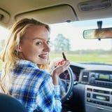 Mujer que aplica el lápiz labial en un coche mientras que conduce Foto de archivo libre de regalías