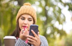 Mujer que aplica el lápiz labial que mira el teléfono como adentro un espejo Imagenes de archivo