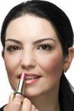 Mujer que aplica el lápiz labial rosado Imagen de archivo