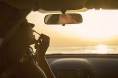 Mujer que aplica el lápiz labial y que usa el espejo retrovisor en coche en la puesta del sol Fotos de archivo