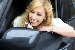 Mujer que aplica el lápiz labial en espejo de coche Imagen de archivo libre de regalías