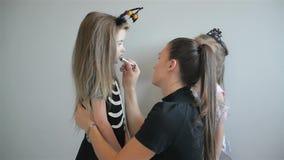Mujer que aplica el maquillaje de Halloween a la cara de sus hijas Se divierten mucho que pasan el tiempo junto Buen humor metrajes