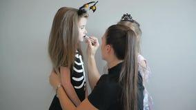 Mujer que aplica el maquillaje de Halloween a la cara de sus hijas Se divierten mucho que pasan el tiempo junto almacen de metraje de vídeo