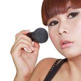 Mujer que aplica el polvo en mejilla con el cepillo Foto de archivo libre de regalías