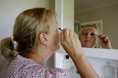 Mujer que aplica el rimel Foto de archivo