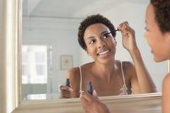 Mujer que aplica el rimel en espejo en casa Fotografía de archivo