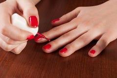 Mujer que aplica esmalte de uñas del color rojo en la tabla de madera Fotografía de archivo libre de regalías