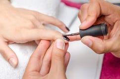 Mujer que aplica esmalte de uñas negro Foto de archivo libre de regalías