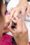 Mujer que aplica esmalte de uñas negro Imagenes de archivo
