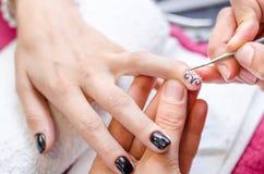 Mujer que aplica esmalte de uñas negro del dibujo Imagenes de archivo