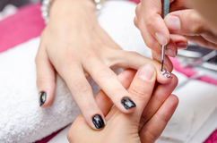Mujer que aplica esmalte de uñas negro del dibujo Foto de archivo libre de regalías