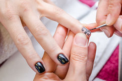 Mujer que aplica esmalte de uñas negro del dibujo Foto de archivo