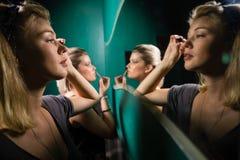 Mujer que aplica lápiz de ojos mientras que mira el espejo Fotografía de archivo libre de regalías