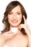 Mujer que aplica la crema imagen de archivo