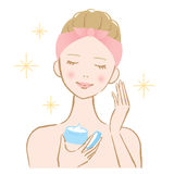 Mujer que aplica la crema cosmética en su cara Imagenes de archivo