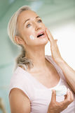 Mujer que aplica la crema de cara Imagenes de archivo