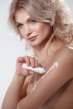 Mujer que aplica la crema de la crema hidratante Foto de archivo libre de regalías