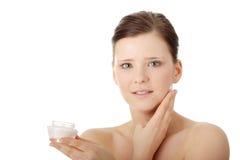 Mujer que aplica la crema de la crema hidratante en cara Foto de archivo libre de regalías