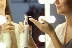 Mujer que aplica la crema de la crema hidratante en las manos Imágenes de archivo libres de regalías