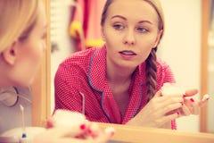 Mujer que aplica la crema de piel hidratante Skincare Imagenes de archivo