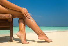 Mujer que aplica la crema del sunblock en la pierna en la playa tropical hermosa Fotos de archivo