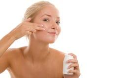 Mujer que aplica la crema en cara Foto de archivo libre de regalías