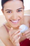 Mujer que aplica la crema en su cara Imagen de archivo