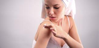 Mujer que aplica la crema en su carrocería Imagenes de archivo