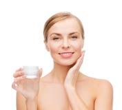 Mujer que aplica la crema en su piel fotos de archivo