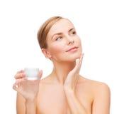 Mujer que aplica la crema en su piel imagen de archivo libre de regalías